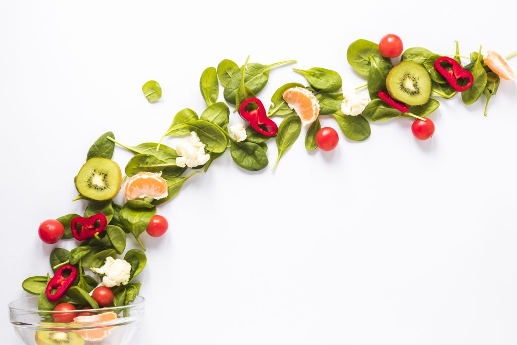 Fresh vegetables and fruits arranged in curved shaped on white backdrop