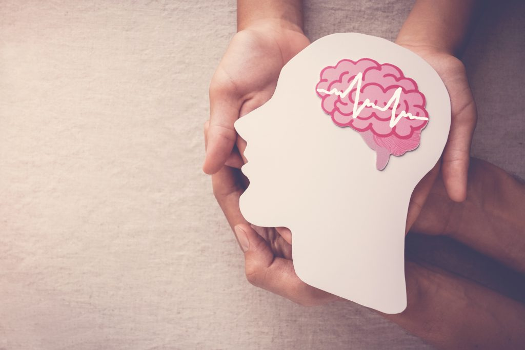 Adult and child hands holding encephalography brain paper cutout. A picture depicting the mental health benefits