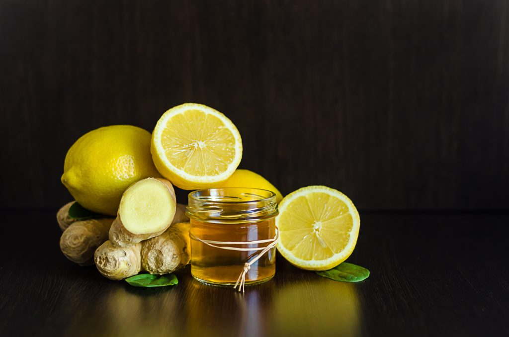 honey, lemon, ginger for boosting immunity for colds, flu, epidemic on dark wooden background with copy space, soft focus. Image aims at depicting the health benefits of vitamin c.