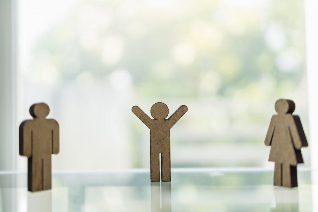 Social Distancing Concept for Coronavirus 2019 disease (COVID-19). Wooden man and woman icon figure standing with distance to other people on table with copy space.