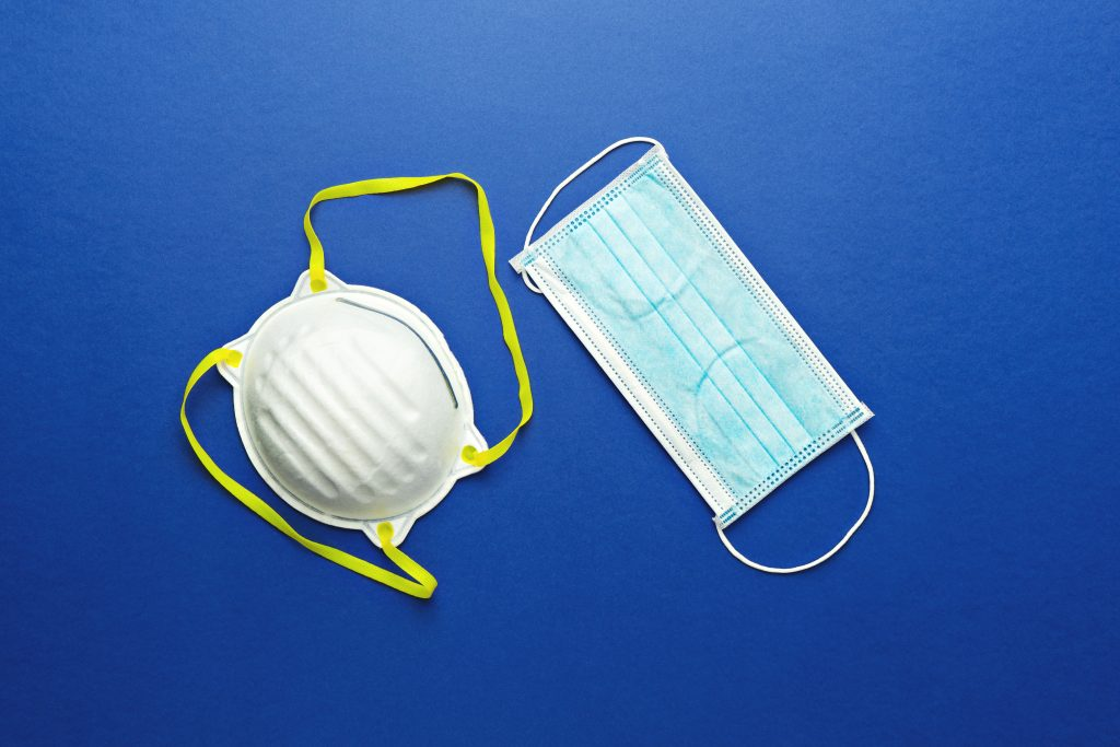 Two types of protective face masks on blue background. Protective masks used to stay safe from the coronavirus