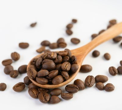 "alt=""coffee beans in a wooden spoon on a white wood table"""